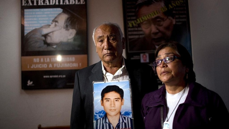 Javier Roca and Ricardina Andagua pose for the picture with the portrait of their son Martin, a student that was detained and disappeared by security forces in 1993, after a press conference in Lima, Peru, Wednesday, Sept. 28, 2016. Former Peruvian spy chief Vladimir Montesinos has been sentenced to 22 years in prison for the forced disappearance of Martin Andagua, a professor and a fellow student in 1993. (AP Photo/Rodrigo Abd)