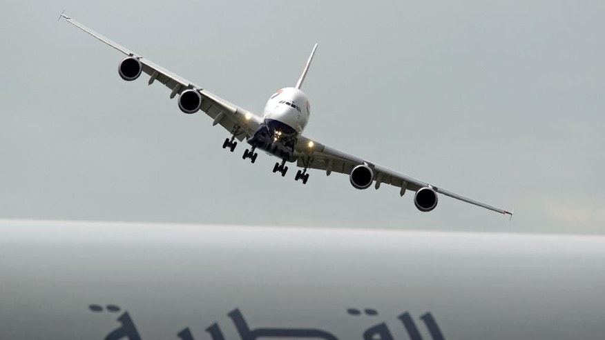 FILE- In this Tuesday June 18, 2013 file photo, a British Airways Airbus A380 prepares to land after performing its demonstration flight, at the 50th Paris Air Show at Le Bourget airport, north of Paris. A Qatar Airways Boeing Dreamliner is visible at foreground. Qatar Airways and the parent of British Airways are intensifying their relationship by setting up a revenue-sharing business partnership that will see them cooperating on scheduling and ticket prices. (AP Photo/Remy de la Mauviniere, File)