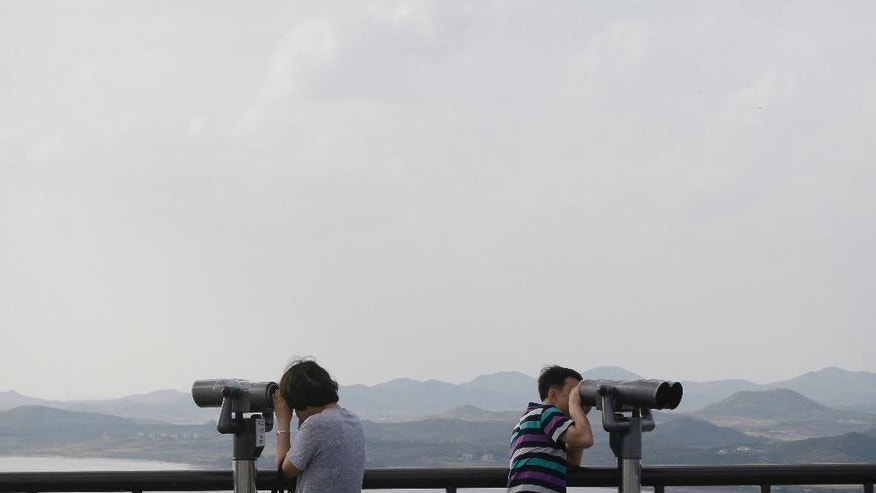 Visitors use binoculars to view the North Korean territory, at the unification observation in Paju, near the border with North Korea, South Korea, Thursday, Sept. 29, 2016. South Korea's military said Thursday that a North Korean soldier had crossed the border between the rivals to defect. (AP Photo/Ahn Young-joon)