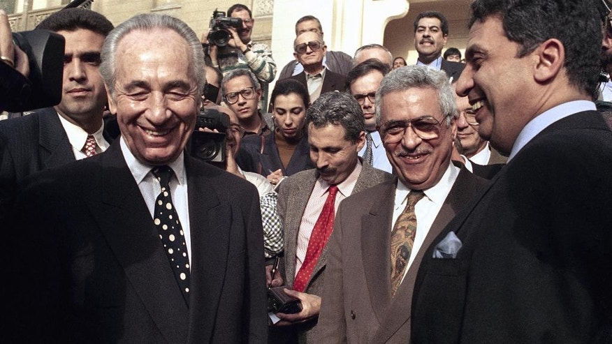 FILE - In this Wednesday, Dec. 29, 1993, file photo, Israeli Foreign Minister Shimon Peres, left, is all smiles along with PLO negotiator Mahmoud Abbas, second from right, and Egyptian Foreign Minister Amr Moussa, right, after talks in Cairo. Peres, a former Israeli president and prime minister, whose life story mirrored that of the Jewish state and who was celebrated around the world as a Nobel prize-winning visionary who pushed his country toward peace, has died, the Israeli news website YNet reported early Wednesday, Sept. 28, 2016. He was 93. (AP Photo, File)
