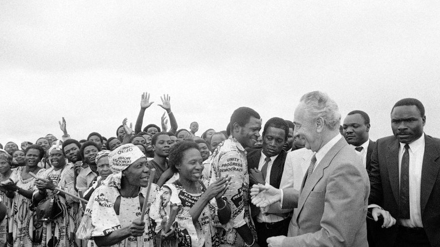 FILE - In this Aug. 25, 1986, file photo, Israeli Prime minister Shimon Peres is greeted by a large group of dancers at the airport in Cameroon, where he went to announce the restoration of diplomatic relations after 13 years. Peres, a former Israeli president and prime minister, whose life story mirrored that of the Jewish state and who was celebrated around the world as a Nobel prize-winning visionary who pushed his country toward peace, has died, the Israeli news website YNet reported early Wednesday, Sept. 28, 2016. He was 93. (AP Photo/Anat Givon, File)