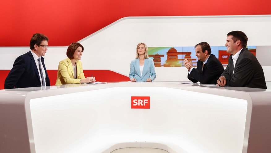 The leaders of Switzerland's four main parties: Albert Roesti, SVP (right wing Swiss People's Party), Petra Goessi, FDP (Liberals), TV host Nathalie Christen, Gerhard Pfister, CVP (Christian Democratic People's Party), and Christian Levrat, SP (Socialist Party), from left, preparing to debate the intelligence law and other issues.