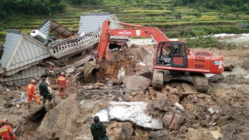 Rescuers use heavy equipment to dig in the rubble of a house that was destroyed in a landslide in Sucun village in eastern China's Zhejiang Province Thursday, Sept. 29, 2016. Several dozen people were reported missing Thursday after rain-saturated hillsides collapsed onto villages in China following a typhoon. (Chinatopix via AP)