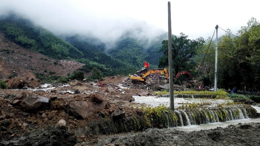 Rescuers use heavy equipment to search for survivors following a landslide in Sucun village in eastern China's Zhejiang Province Thursday, Sept. 29, 2016. Several dozen people were reported missing Thursday after rain-saturated hillsides collapsed onto villages in China following a typhoon. (Chinatopix via AP)