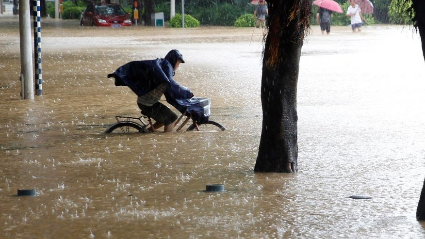 A man bicycles through a flooded street after the landfall of Typhoon Megi in Fuzhou in southeastern China's Fujian Province Wednesday, Sept. 28, 2016. A massive typhoon made landfall in eastern China Wednesday, a day after carrying strong winds over Taiwan that felled trees and scattered debris, killing several people and injuring hundreds. (Chinatopix via AP)