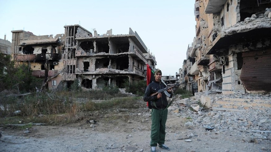 FILE - In this Feb. 23, 2016 file photo, a civilian fighter holding the Libyan flag stands in front of damaged buildings in Benghazi, Libya. Amnesty International, an international rights group expressed alarm Friday, Sept. 30, 2016, over the fate of hundreds of Libyan and foreign nationals trapped for months amid fighting in the eastern city of Benghazi. Amnesty International said that nearly 130 families and hundreds of foreigners in the southwestern Benghazi neighborhood of Ganfouda have been cut off from the outside world, with dwindling food and fuel supplies. (AP Photo/Mohammed el-Shaiky, File)