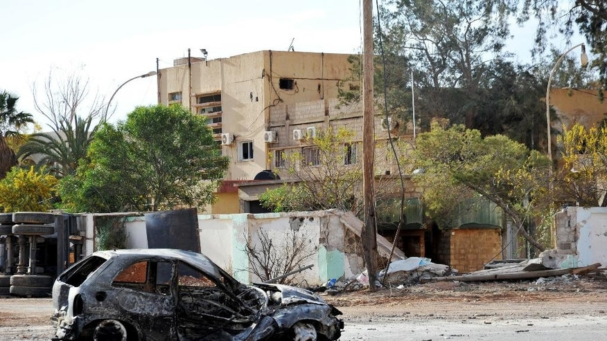 FILE -- In this March 10, 2016 file photo, damaged buildings and a burnt out car are seen in the Hawari area, south-west of the city of Benghazi, Libya. Amnesty International, an international rights group expressed alarm Friday, Sept. 30, 2016, over the fate of hundreds of Libyan and foreign nationals trapped for months amid fighting in the eastern city of Benghazi. Amnesty International said that nearly 130 families and hundreds of foreigners in the southwestern Benghazi neighborhood of Ganfouda have been cut off from the outside world, with dwindling food and fuel supplies. (AP Photo/Mohammed Elshaiky, File)