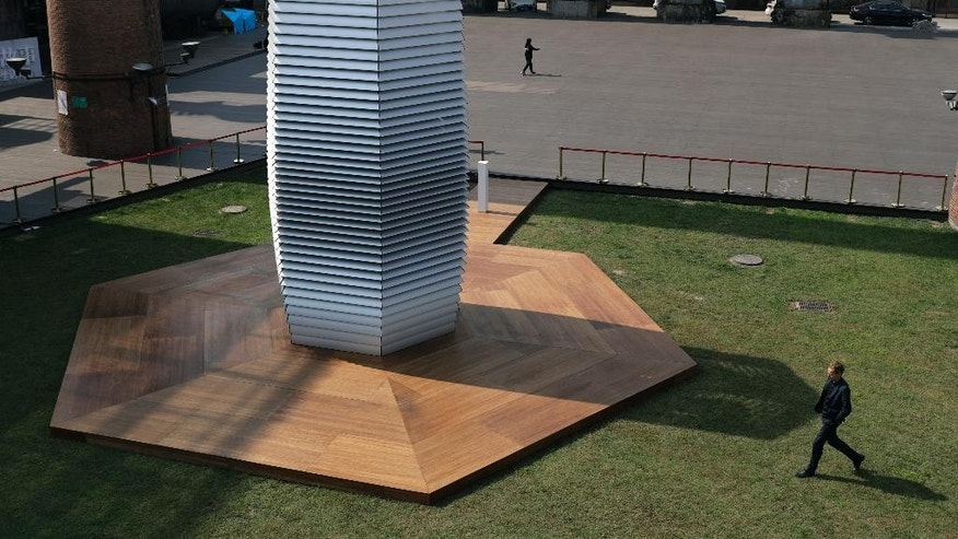 Dutch artist Daan Roosegaarde, right, walks by his Smog Free Tower on display at D-751art district in Beijing, Thursday, Sept. 29, 2016. In a city where smog routinely blankets the streets and chokes off clean air, Roosegaarde has offered an eccentric solution: a 20-foot metal tower that takes in smog and purifies it like a giant outdoor vacuum cleaner. (AP Photo/Andy Wong)