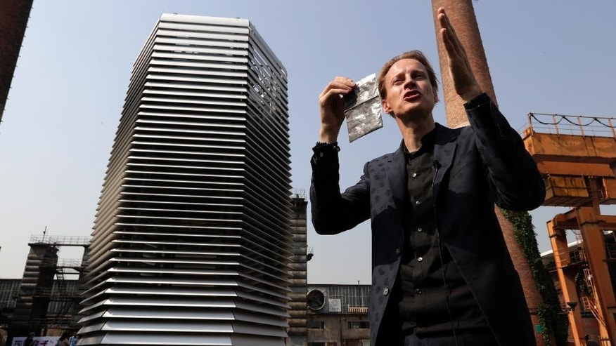 Dutch artist Daan Roosegaarde holds a packet containing smog particles collected by the Smog Free Tower as he presents his machine at D-751art district in Beijing, Thursday, Sept. 29, 2016. In a city where smog routinely blankets the streets and chokes off clean air, a Dutch artist has offered an eccentric solution: a 20-foot metal tower that takes in smog and purifies it like a giant outdoor vacuum cleaner. (AP Photo/Andy Wong)
