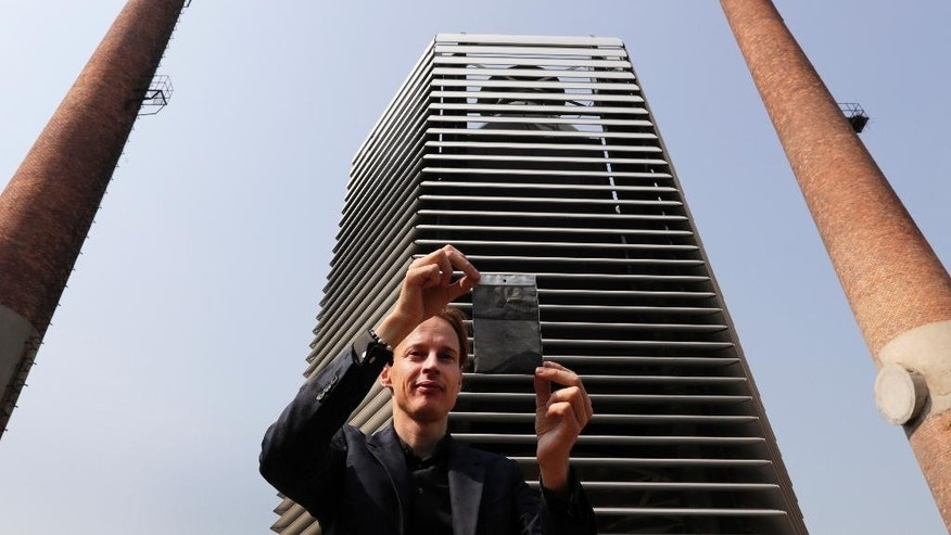 Dutch artist Daan Roosegaarde shows smog particles collected by the Smog Free Tower on display in between chimney stacks as he presents his machine at D-751art district in Beijing, Thursday, Sept. 29, 2016. In a city where smog routinely blankets the streets and chokes off clean air, a Dutch artist has offered an eccentric solution: a 20-foot metal tower that takes in smog and purifies it like a giant outdoor vacuum cleaner. (AP Photo/Andy Wong)