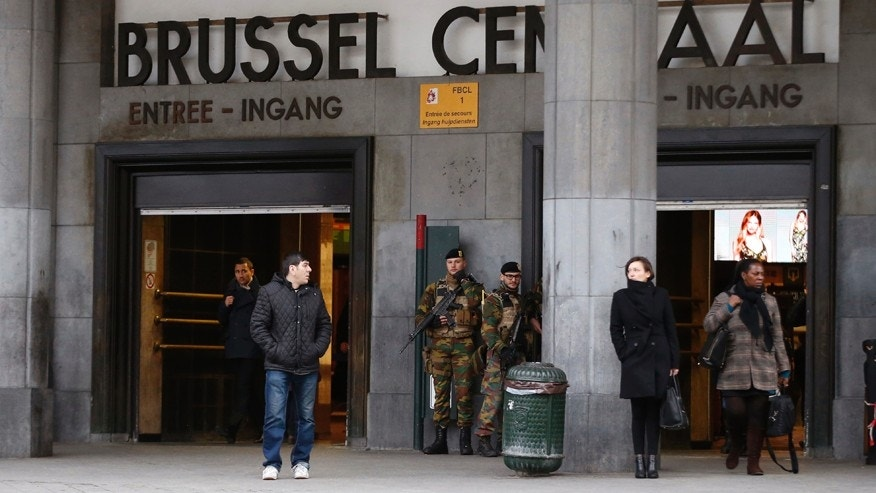 Commuters walk past soldiers on duty at Brussels Central Station as they return to work in Brussels.