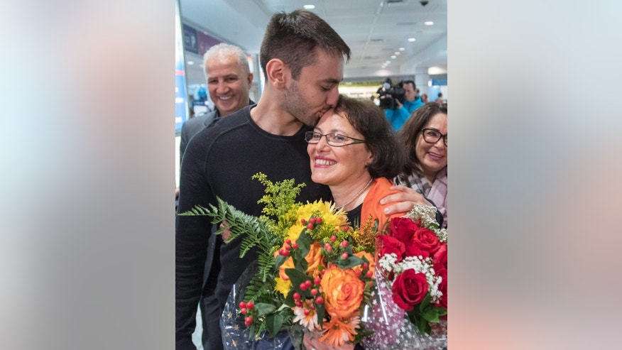 Homa Hoodfar gets a kiss from her nephew Saam Hamzavi as she arrives at Trudeau Airport Thursday, Sept. 29, 2016, in Montreal. Hoodfar, a Canadian-Iranian academic was held in Iran's Evin prison for more than 100 days before being released on Monday. (Ryan Remiorz/The Canadian Press via AP)
