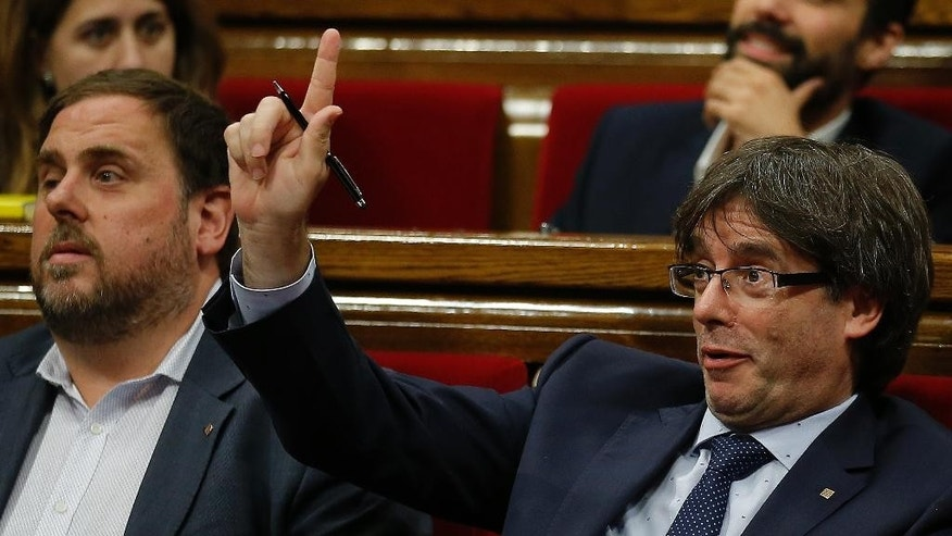 President of Catalonia Carles Puigdemont, right, gestures during a debate on his presidency at the Parliament in Barcelona, Spain, Thursday, Sept. 29, 2016. Catalan regional lawmakers are debating regional President Carles Puigdemont's latest promise to hold another independence referendum next September with or without agreement from Spain. Puigdemont launched the proposal Wednesday during a debate on his presidency, saying he would seek Spain's backing but intended holding it anyway if Spain persists in ruling it out. (AP Photo/Manu Fernandez)