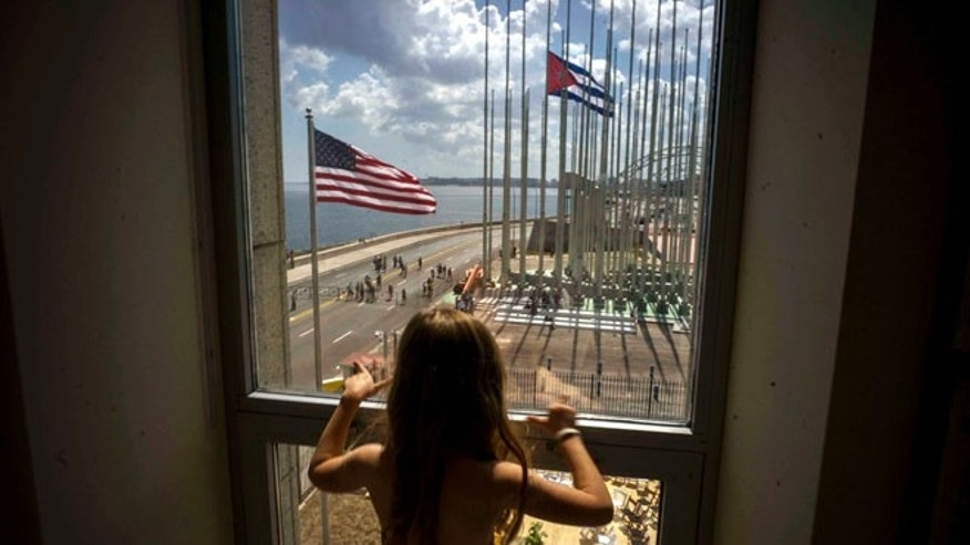 "FILE - In this Aug. 14, 2015 file photo, a girl looks out from the newly opened U.S. Embassy after the U.S. flag raising ceremony in Havana, Cuba, as part of officially restored diplomatic relations. U.S. presidential candidate Donald Trump had been generally supportive of the normalization of relations with Cuba, but on Friday, Sept. 16, 2016 the Republican nominee pledged to reverse Obama's series of executive orders unless Cuba's President Raul Castro meets demands including ""religious and political freedom for the Cuban people and the freeing of political prisoners."" (AP Photo/Ramon Espinosa, File)"