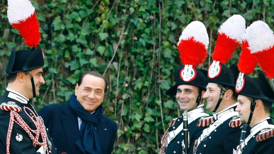 FILE -- In this file photo taken on March 25, 2009, Silvio Berlusconi, then Italian Premier, jokes with Carabinieri paramilitary police officers as he waits for the arrival of Sweden's Royals, at Rome's Villa Madama. Silvio Berlusconi is marking his 80th birthday quietly with his family, amid a flurry of greetings and reflections on his influence over a political career spanning three decades. (AP Photo/Alessandra Tarantino)