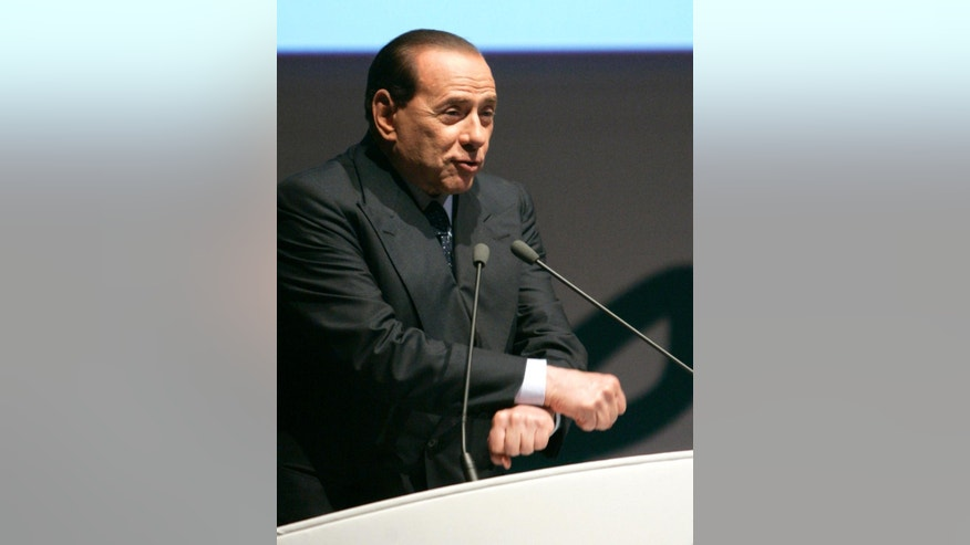 FILE -- In this file photo taken on June 25, 2008, Silvio Berlusconi, then Italian Premier, gestures miming handcuffs as he speaks during the Confesercenti traders association's annual assembly in Rome. Silvio Berlusconi is marking his 80th birthday quietly with his family, amid a flurry of greetings and reflections on his influence over a political career spanning three decades. (AP Photo/Riccardo De Luca)
