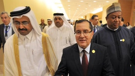 In this photo dated Wednesday, Sept. 28, 2016, Algerian Energy Minister Noureddine Boutarfa, center, gestures as he leaves the International Conference Center in Algiers, Algeria, with Minister of Energy and Industry of Qatar, Bin Saleh Al-Sada, left, and acting Secretary General of OPEC Mohammed Barkindo, after a meeting of oil ministers of the Organization of the Petroleum Exporting countries, OPEC, in Algiers, Algeria. OPEC nations reached a preliminary agreement Wednesday to curb oil production for the first time since the global financial crisis eight years ago, in an effort to reduce a global glut of crude that has depressed oil prices for more than two years and weakened the economies of oil-producing nations. (AP Photo/Sidali Djarboub)
