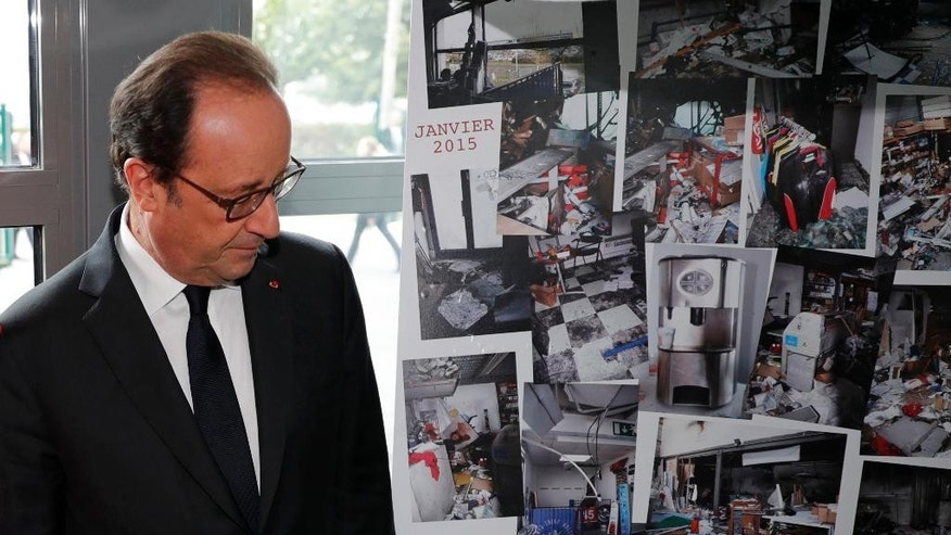 French President Francois Hollande walks past photographs of the devastated printing plant after the attack, as the plant reopens Thursday.