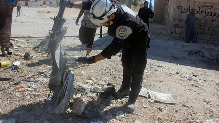 In this photo provided by the Syrian Civil Defense group known as the White Helmets, shows members of Civil Defense inspecting the cluster bombs in the Khan Sheikhoun neighborhood of Idlib, Syria, Thursday, Sept. 29, 2016. The U.S. and Russia escalated their war of words over Syria Thursday as government forces kept up their assault on Aleppo's rebel-held quarters and registered tenuous gains. (Syrian Civil Defense White Helmets via AP)