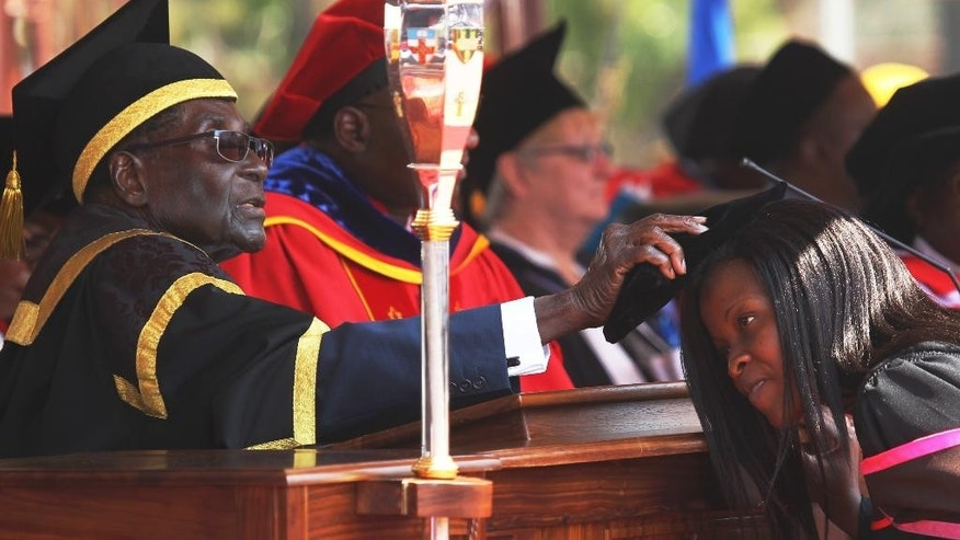 Zimbabwean President Robert Mugabe, left, places a cap on a student at the University of Zimbabwe, during graduation ceremony in Harare, Thursday, Sept, 29, 2016. (AP Photo/Tsvangirayi Mukwazhi)