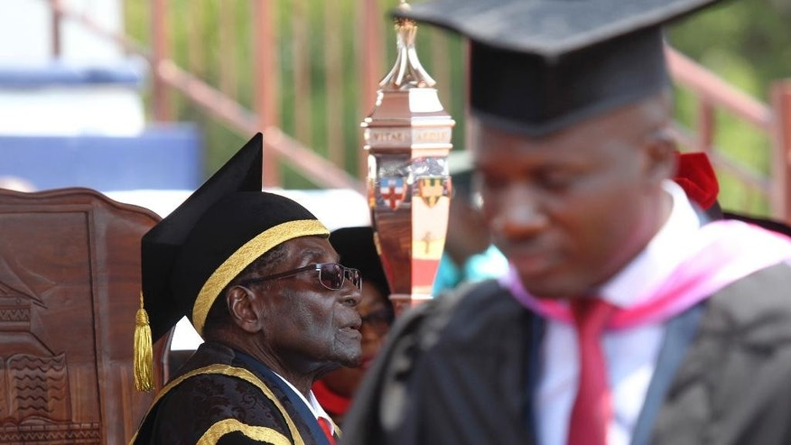 A University of Zimbabwe student walks past Zimbabwean President Robert Mugabe after being capped at a graduation ceremony in Harare, Thursday, Sept, 29, 2016. (AP Photo/Tsvangirayi Mukwazhi)