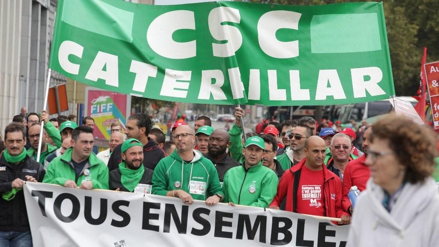 Trade Union workers from the Caterpillar company march during a general strike in Brussels on Thursday, Sept. 29, 2016. Demonstrators marched on Thursday against cost cutting measures and government reforms. (AP Photo/Olivier Matthys)