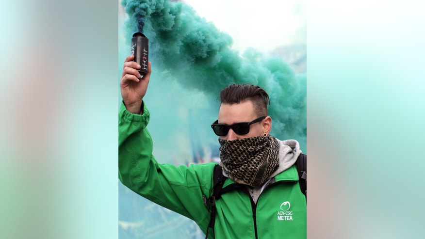 A protestor releases a colored smoke canister as he marches during a general strike in Brussels on Thursday, Sept. 29, 2016. Demonstrators marched on Thursday against cost cutting measures and government reforms. (AP Photo/Olivier Matthys)