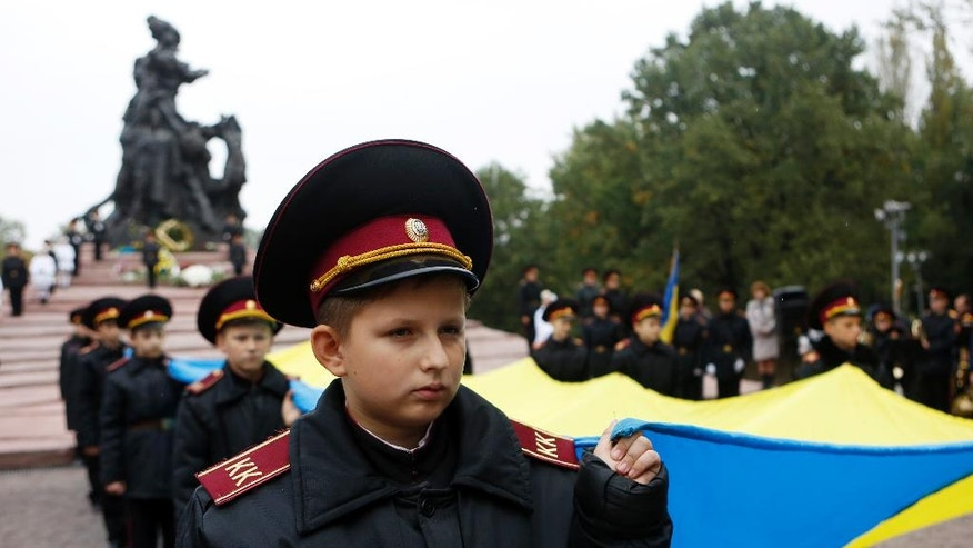 Kiev Cadets hold the national flag of Ukraine during commemoration events in Babi Yar ravine where Nazi troops machine-gunned tens of thousands of Jews during WWII, in Kiev, Ukraine, Thursday, Sept. 29, 2016. Ukraine marked the 75th anniversary of the 1941 Babi Yar massacre. (AP Photo/Sergei Chuzavkov)