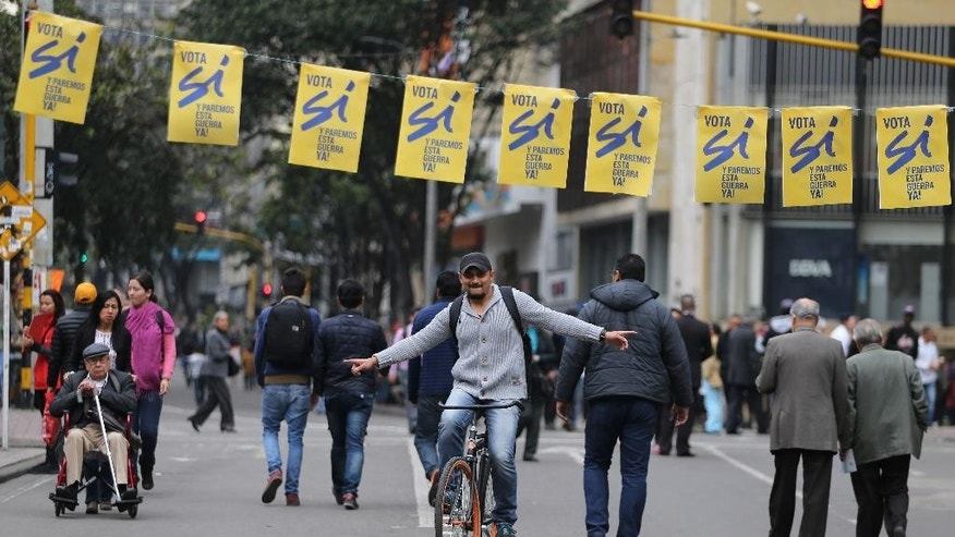 "A man cycles under banners supporting the ""yes"" vote in an upcoming referendum on the peace deal between the government and rebels of the Revolutionary Armed Forces of Colombia, FARC, in Bogota, Colombia, Thursday, Sept. 29, 2016. Colombians go to the polls on Oct. 2 in a referendum where they will be asked to ratify or reject the deal. (AP Photo/Fernando Vergara)"
