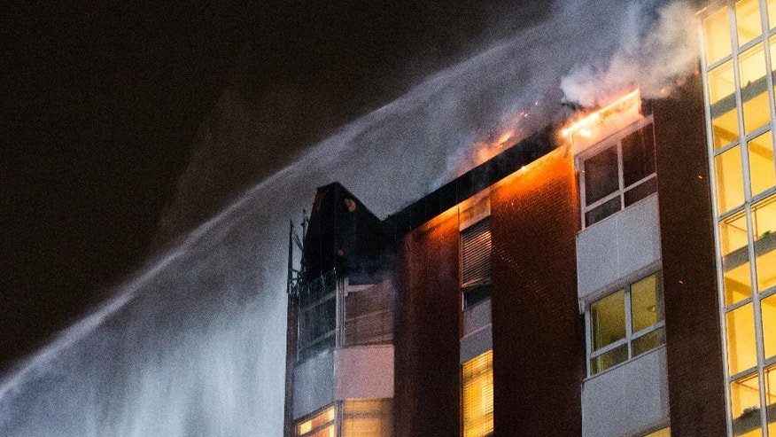 Flames emanate from the roof of the Bergmannsheil hospital in Bochum, western Germany, Friday morning, Sept. 30, 2016 after a fire broke out. At least two people died in the fire. (Marcel Kusch/dpa via AP)