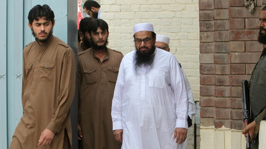 Hafiz Saeed, center, leader of Jamaat-ud-Dawa arrives to address an anti-Indian rally in Lahore, Pakistan, Friday, Sept. 30, 2016. The founding member of banned Lashkar-e-Taiba militant group and head of its charity Jamaat-ud-Dawa has pledged to take revenge on India for killing innocent Kashmiri people. (AP Photo/K.M. Chaudary)