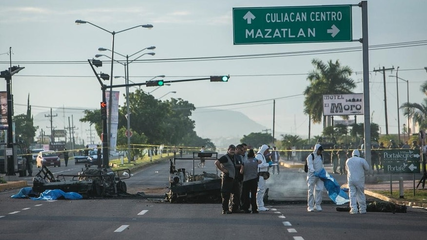 "Police investigators examine the site where a military convoy was ambushed using grenades and high-powered guns, killing five soldiers in the city of Culiacan, Mexico, Friday, Sept. 30, 2016. Local military commander Gen. Alfonso Duarte said it is very probable that the attack was carried out by the sons of imprisoned drug lord Joaquin ""El Chapo"" Guzman. (AP Photo/Rashide Frias)"