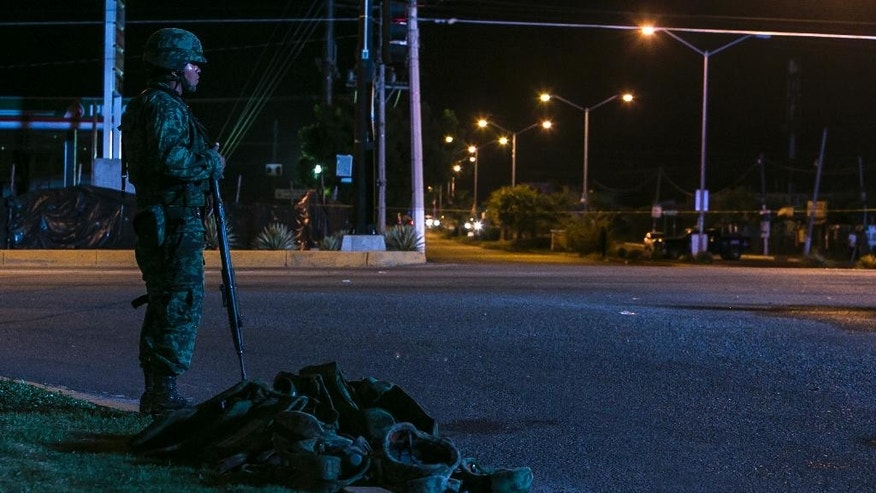 "A solider stand guards next to army uniforms and weapons that were gathered after a military convoy was ambushed using grenades and high-powered guns, killing five soldiers in the city of Culiacan, Mexico, early Friday, Sept. 30, 2016. Local military commander Gen. Alfonso Duarte said it is very probable that the attack was carried out by the sons of imprisoned drug lord Joaquin ""El Chapo"" Guzman. (AP Photo/Rashide Frias)"