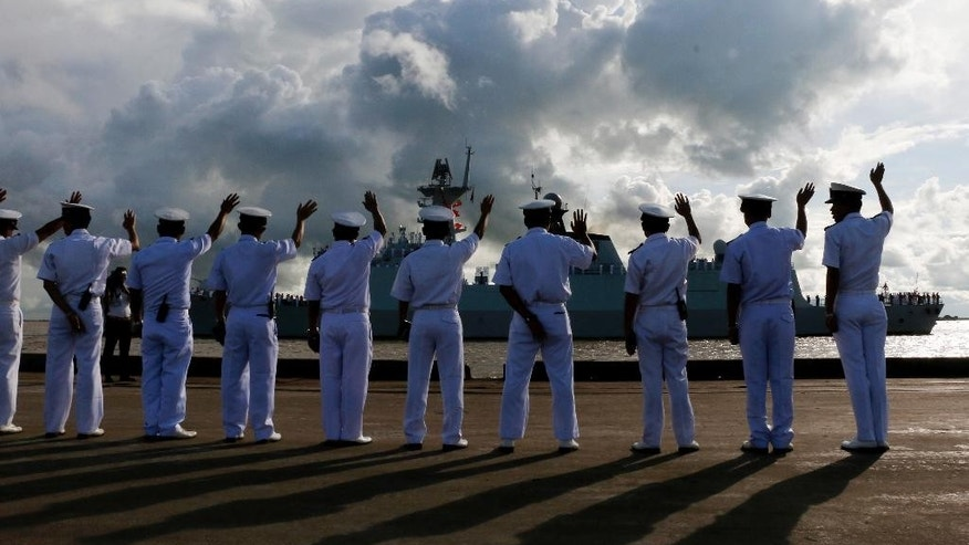 Myanmar navy officers wave to welcome the arrival of a Chinese navy ship Friday, Sept. 30, 2016, in Yangon, Myanmar. Two Chinese frigates, the Zhoushan and the Xiangtan, are both paying a friendly port call at the Thilawa port in Myanmar's old capital Yangon. (AP Photo/Thein Zaw)