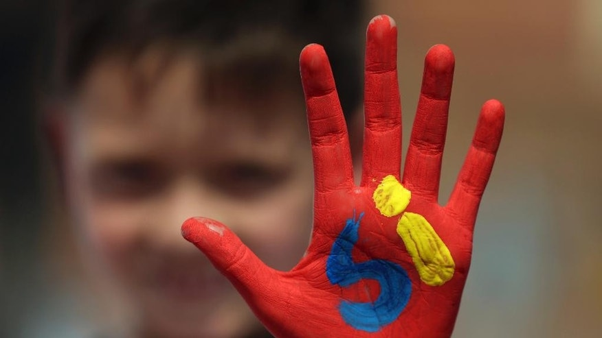 """A boy shows his hand painted with the word """"Yes"""" in Spanish during an event attended by Colombia's President Juan Manuel Santos to promote the """"yes"""" vote in the upcoming referendum on the peace deal he signed with rebels  Revolutionary Armed Forces of Colombia, FARC, in Soacha, in the outskirts of Bogota, Colombia, Friday, Sept. 30, 2016.  Colombians go to the polls on Oct. 2 in a referendum where they will be asked to ratify or reject the accord. (AP Photo/Fernando Vergara)"""