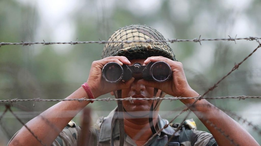 FILE - In this Sept. 24, 2016 file photo, an Indian Border Security Force soldier looks at the Pakistan side of the border through a binocular at Ranbir Singh Pura, about 35 kilometers (22 miles) from Jammu, India. In New Delhi, they say that highly trained Indian soldiers slipped across the de facto border and into Pakistani-controlled Kashmir in a daring nighttime raid, killing anti-India militants preparing to launch attacks. In Islamabad, they say that only one Indian soldier made it across the border, and he was captured, with Pakistani forces easily driving back the other Indians, who retreated as soon as they encountered resistance. The dueling tales of courageous forces serve politics on both sides of the border, with powerful forces in each country able to proclaim their courage in the face of aggression. (AP Photo/Channi Anand, File)