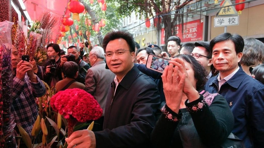In this Jan. 28, 2014 photo, people take smartphone photos of Wan Qingliang, center, then-Communist Party chief of Guangzhou, in southern China's Guangdong province. A pair of formerly high-flying Chinese provincial officials, Wan and Wang Min, were sentenced to life in prison Friday, Sept. 30, 2016, for corruption and bribe-taking, the latest targets to fall in President Xi Jinping's years-long campaign against graft at all levels of government and state industry. (Chinatopix via AP)