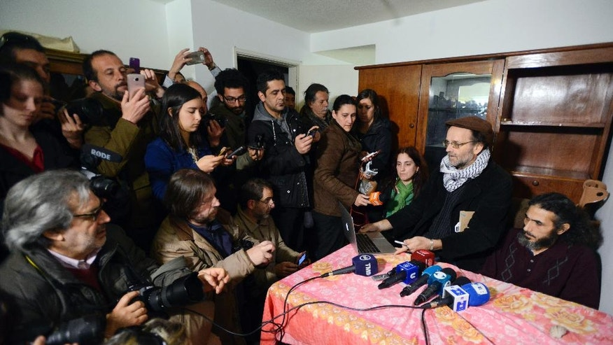 Journalists crowd round a table for a press conference called by former Guantanamo detainee Syrian Abu Wa'el Dhiab, in his apartment in Montevideo, Uruguay, Friday, Sept. 30, 2016, where he said he is going to stop drinking water on Monday, to press officials into speeding up his relocation to another country. Uruguay's government says it is searching for another country to take Dhiab. Dhiab, who is currently on a hunger strike, says they are taking too long to relocate him. (AP Photo/Matilde Campodonico)