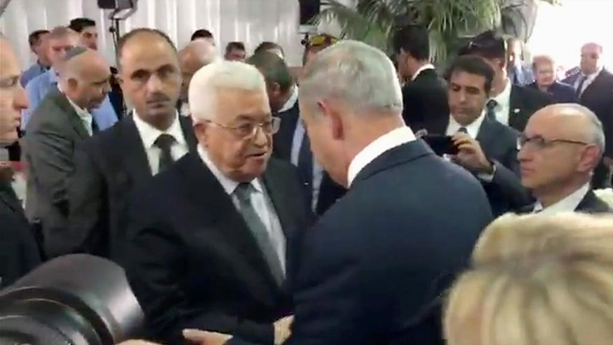 This image made from video released by the Israeli Prime Minister's office shows Palestinian President Mahmoud Abbas, left, shaking hands with Israeli Prime Minister Benjamin Netanyahu, right, at the funeral for former President Shimon Peres in Jerusalem, Friday, Sept. 30, 2016. Shimon Peres was being laid to rest on Friday in a ceremony attended by thousands of admirers and dozens of international dignitaries — in a final tribute to a man who personified the history of Israel during a remarkable seven-decade political career and who came to be seen by many as a visionary and symbol of hopes of Mideast peace. (Israel Prime Minister's office via AP)