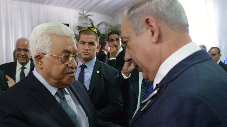 This image released by the Israeli Government Press Office shows Palestinian President Mahmoud Abbas, left, shaking hands with Israeli Prime Minister Benjamin Netanyahu, right, at the funeral for former President Shimon Peres in Jerusalem, Friday, Sept. 30, 2016. Shimon Peres was being laid to rest on Friday in a ceremony attended by thousands of admirers and dozens of international dignitaries — in a final tribute to a man who personified the history of Israel during a remarkable seven-decade political career and who came to be seen by many as a visionary and symbol of hopes of Mideast peace. (Amos Ben Gershom, Israeli Government Press Office via AP)