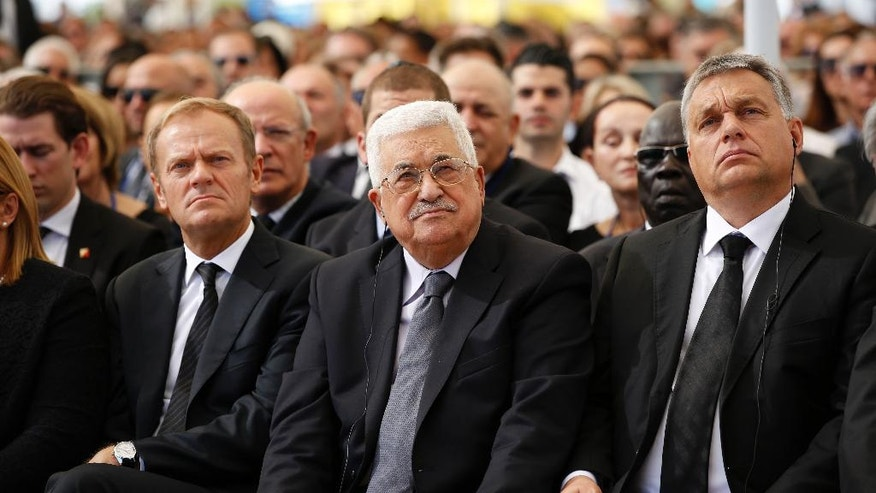 Palestinian President Mahmoud Abbas, center, sits next to European Council President Donald Tusk, left, during the funeral of former Israeli President Shimon Peres at Mt. Herzl Military Cemetery in Jerusalem, Friday, Sept. 30, 2016. (Abir Sultan/Pool Photo via AP)