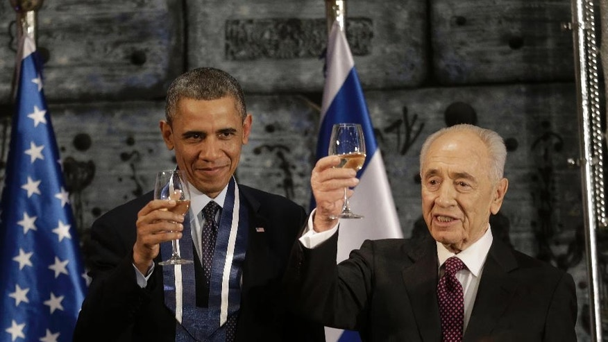 FILE - In this March 21, 2013 file photo, President Barack Obama and Israeli President Shimon Peres raise their glasses in a toast after Obama received the Israeli Medal of Distinction from Peres during a State Dinner at President's residence in Jerusalem, Israel. Both were Nobel Prize laureates who labored for peace in the Middle East but failed to achieve it. Now, their joint efforts are at an end as President Barack Obama prepares to pay a final tribute to Shimon Peres in Jerusalem. Obama boarded Air Force One Thursday, Sept. 29, 2016, to fly to Israel to join dozens of world leaders at the funeral of Peres, the 93-year-old former prime minister, president and elder statesman.  (AP Photo/Pablo Martinez Monsivais, File)