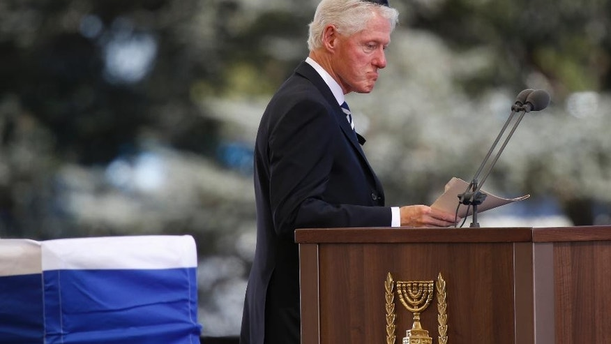 Former US President Bill Clinton passes the flag-draped coffin of former Israeli President Shimon Peres during his funeral at the Mount Herzel national cemetery in Jerusalem, Friday, Sept. 30, 2016. (AP Photo/Ariel Schalit)