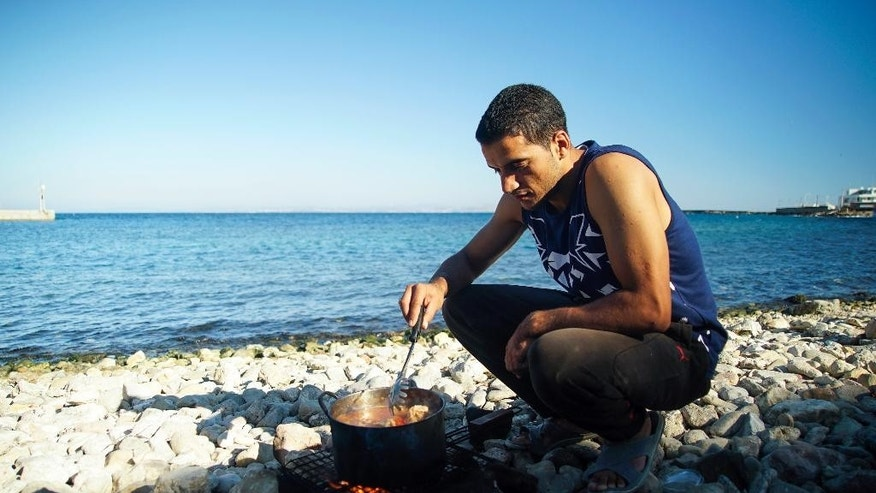 A migrants cooks on the beach, on the northeastern Greek island of Chios, Thursday, Sept. 29, 2016. More than 3,500 refugees and migrants are stuck on Chios island, since the European border closures earlier this year. (AP Photo/Mstyslav Chernov)