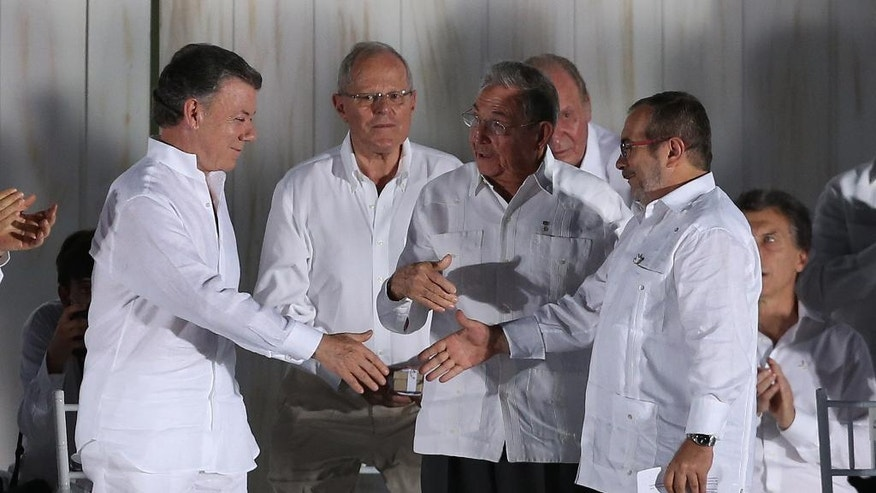FILE - In this Sept, 26, 2016 file photo, the top commander of the Revolutionary Armed Forces of Colombia, FARC, Rodrigo Londono, right, shakes hands with Colombia's President Juan Manuel Santos, left, as Cuba's President Raul Castro, center, looks on after they signed a peace agreement between the government and the FARC in Cartagena, Colombia. Guessing the winner of the Nobel Peace Prize is notoriously hard because the secretive Norwegian Nobel Committee isn't dropping any hints, except that 376 people and groups have been nominated for the award, which will be announced on Oct. 10. That doesn't stop Nobel watchers from speculating, sometimes based on their own preferences or the small number of nominations that were made public by those who submitted them. Opposite sides of a violent conflict sitting down to make peace , it's hard to find anything that better embodies the spirit of the Nobel Peace Prize. (AP Photo/Fernando Vergara, File)