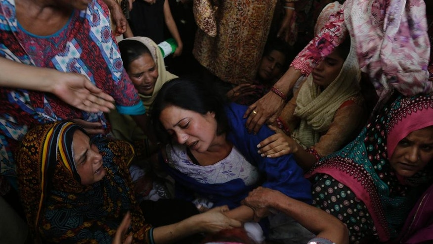 FILE - In this Monday, March 28, 2016 photo, women try to comfort a Christian mother who lost her son in bomb attack, claimed responsibility by Jamaat-ul-Ahrar, in Lahore, Pakistan. One of Pakistan's most vicious militant groups, Jamaat-ul-Ahrar, has dramatically stepped its attacks over the past month in what appears to be a backlash to military operations against it. It has eclipsed the Pakistani Taliban as the main militant group in a country where multiple armed extremist factions operate. (AP Photo/K.M. Chaudary, File)