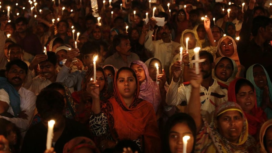 FILE - In this Wednesday, March 30, 2016 Pakistani Christians hold candles during a vigil for victims of a deadly suicide bombing claimed responsibility by Jamaat-ul-Ahrar, in Lahore, Pakistan. One of Pakistan's most vicious militant groups, Jamaat-ul-Ahrar, has dramatically stepped its attacks over the past monthin what appears to be a backlash to military operations against it. It has eclipsed the Pakistani Taliban as the main militant group in a country where multiple armed extremist factions operate. (AP Photo/K.M. Chaudary, File)