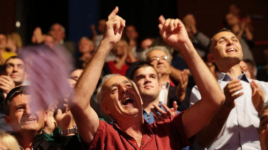 """Bosnian people cheer at a pre election rally of the """"Alliance of Independent Social Democrats"""" party in the Bosnian town of Banja Luka, 240 kms northwest of Sarajevo, Bosnia, on Thursday, Sept. 29, 2016. Bosnians will vote in local elections on Sunday Oct. 2. (AP Photo/Amel Emric)"""