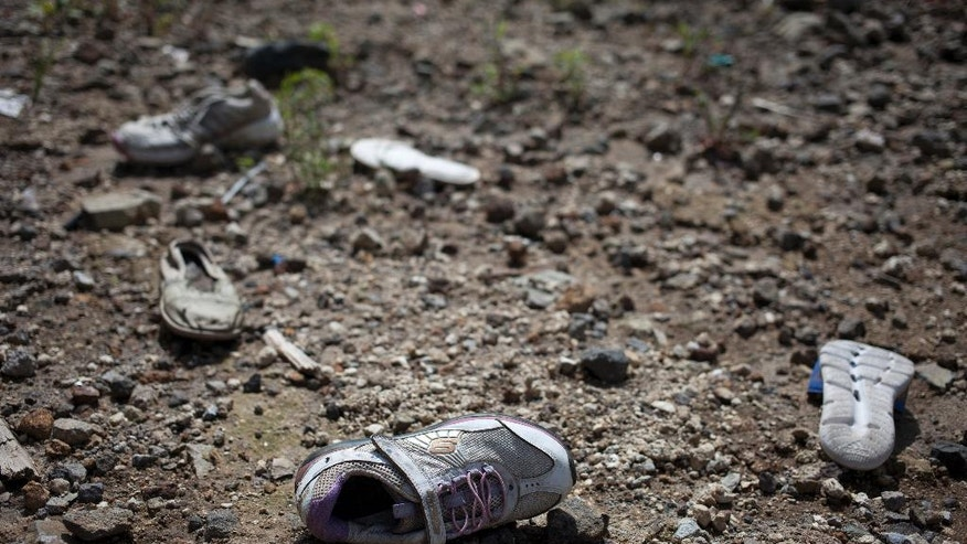 This Sept. 20, 2016 photo shows shoes scattered on the ground near the site where a landslide hit the El Cambray neighborhood one year ago in Santa Catarina Pinula on the outskirts of Guatemala City. One year after a massive landslide killed at least 280 people, abandoned shoes, toys, appliances and clothing litter what is, literally, a graveyard. (AP Photo/Moises Castillo)