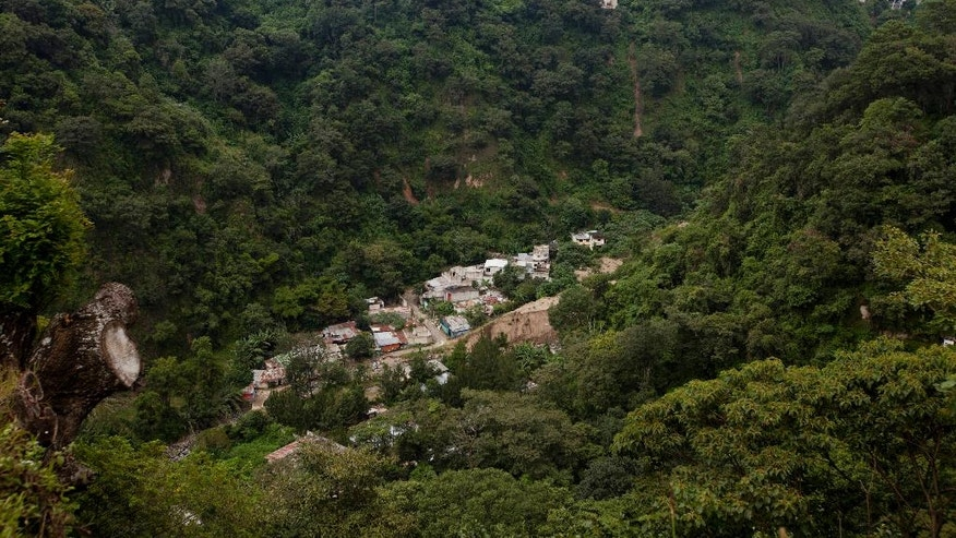 This Sept. 27, 2016 photo shows the abandoned neighborhood El Cambray, bottom, seen from the the Santa Catarina Pinula cemetery where one can also see downtown Guatemala City, one year after a mudslide unleashed at least 105 million cubic feet (3 million cubic meters) of earth on the neighborhood. The official explanation is that the river that runs along the base of the hillside had been diverted into a channel that eroded the slope. (AP Photo/Moises Castillo)